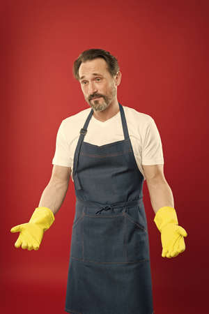 Tradition of quality cleaning. Cleaning man red background. Mature wear rubber gloves and apron. Domestic cleaning. Cleaning service. Housekeeping routine. Household work