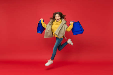 happy running kid with shopping packages after successful day in mall, seasonal discounts Stock Photo