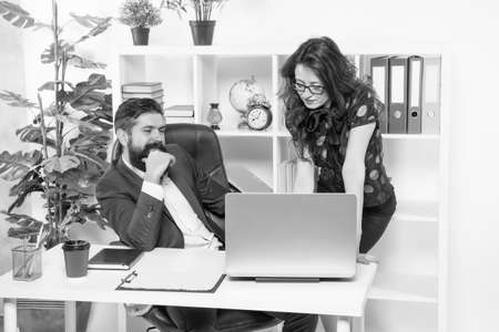 Managers work in modern office. Bearded man and sexy woman use laptop. Using modern computer technologies. Running modern business. Modern life