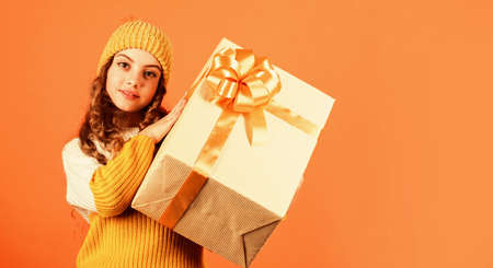 Look at that. small girl knitted hat and sweater. kid hold present box orange background. happy new 2020 year. gift delivery service. shopping advantages. christmas is here. winter holiday surprise