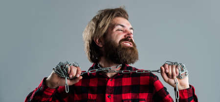 Your life matters. tighten the stranglehold. liberation from slavery. caucasian man has powerful metal chain on neck. handsome man with beard with chain noose. freedom. man chained problems