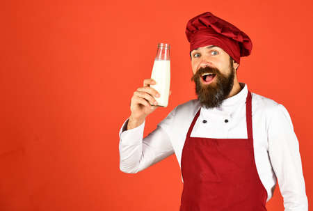Cook with excited face in burgundy uniform holds milk.