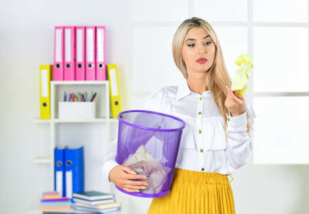 Girl looking for lost document. Cancel file deletion. Dispose of waste paper. Paper recycling. Lost documents. Crumpled paper in basket. Woman digging in garbage bin. Businesswoman hold trash can Banque d'images