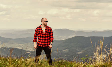 power of nature. man on mountain landscape. camping and hiking. sexy macho man in checkered shirt. countryside concept. farmer on rancho. cowboy in hat outdoor. travelling adventure. hipster fashion