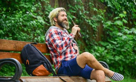 You deserve fine relax. Craft beer. Hipster bearded man hold cold fresh beer bottle. Man enjoying beer in park. Summer rest concept. Guy on bench in park drinking beer. Modern hipster relaxing 免版税图像