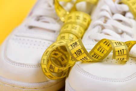Centimeter in yellow color curled on white trainers