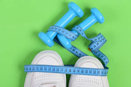 Centimeter in cyan blue color on white trainers and dumbbells