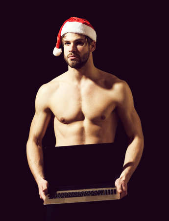 santa muscular man with laptop in hat