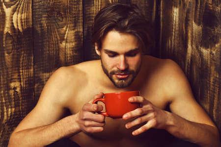 Caucasian bearded sexy macho man holding cup or mug Фото со стока
