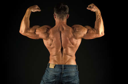 Exercises for back. Bodybuilder perfect shape rear view. Strong bodybuilder flexing arms muscles black background. Fit bodybuilder showing muscular body. Professional coach demonstrate achievements