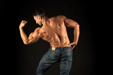 Strong bodybuilder flexing arms muscles black background. Fit bodybuilder showing muscular body. Professional coach demonstrate achievements. Exercises for back. Bodybuilder perfect shape rear view