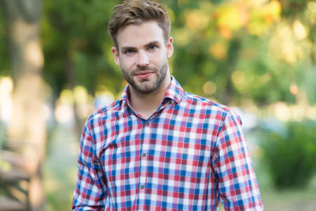 young unshaven man outdoor. male beauty and fashion. guy with bristle wear checkered shirt. concept of barbershop. casual fashion style Banque d'images
