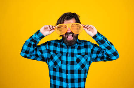 try on a new style. funny and joyful man wear checkered shirt. just having fun. happy brutal party goer. mature bearded hipster in good mood. fashion concept. trendy man in funny party glasses