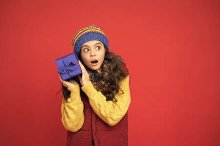 Wish list. Consume consciously. Holidays season. Happy childhood. Christmas gifts and souvenirs. Winter holidays. Happy kid in winter outfit red background. Pick some winter gifts for yourself Stockfoto