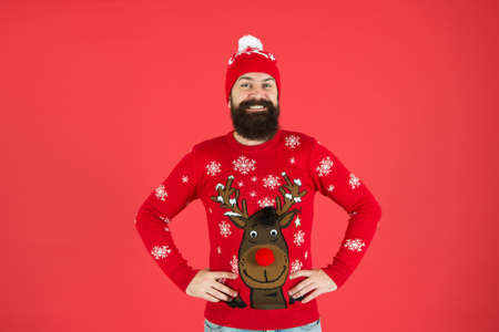 Christmas carols. lets go shopping. time for choosing a gift. should i wear warm clothes. bearded man in knitted accessory. its christmas time. happy new year. smiling hipster red background Stock Photo