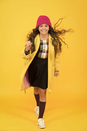 stylish schoolgirl go forward. go to school. happy pupil kid yellow wall. back to school. desire for study. smiling child craving for education. retro and modern school. small girl enjoy autumn