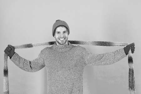 Warm up chilly days with cosy scarf. Happy man wear long scarf. Handsome guy smile with scarf in hands. Fashion accessory for winter. Stylish knit scarf with striped design
