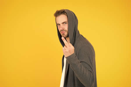 Rude and bad. Rude guy show middle finger yellow background. Rude hand gesture. Sign language. Rude communication. Showing aggression. Antisocial arrogant behavior. Offensive attitude, copy space