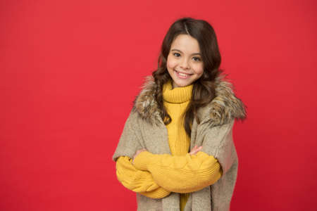 smiling cute kid has long curly hair wearing warm knitted sweater and autumn waistcoat on red background, season style