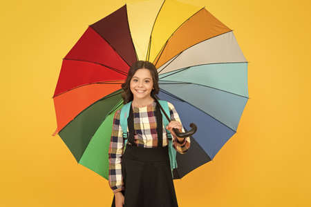 Cheerful smiling schoolgirl. Rainy day fun. Happy walk under umbrella. Enjoy rain concept. Kid girl happy hold colorful rainbow umbrella. Rainy weather with proper garments. On way to school