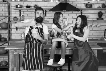 Cooking team. Cook with love. Prepare birthday cake. Friendly family. Mother father and daughter cooking together. Tasks and duties. Child with parents cooking in kitchen. Family preparation food