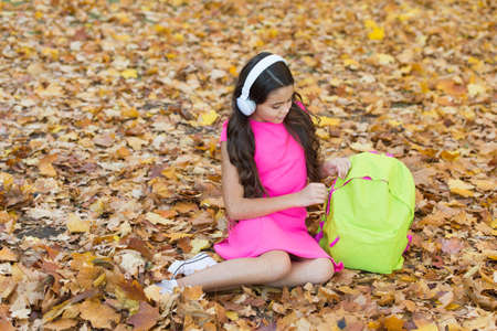 girl in earphones with school bag. kid listen music in autumn park. fall is a time for study. back to school. concept of online education. child sit in autumn leaves