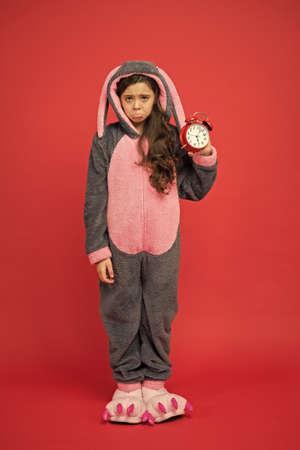 Regular day beginning. Adorable bunny hold alarm clock. Small girl in bunny costume. Child rabbit kigurumi. Girl bunny pajamas. Bunny kid red background. Baby animal. Counting time. Morning alarm