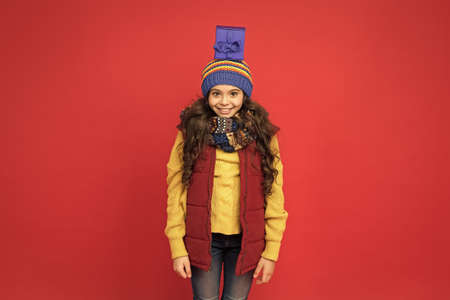 Consume consciously. Holidays season. Happy childhood. Christmas gifts and souvenirs. Winter holidays. Happy kid in winter outfit red background. Pick some winter gifts for yourself. Wish list