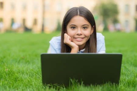 happy kid working on laptop. online education. back to school. teen girl use computer on green grass in park. child with notebook. new technology in modern life. study. Shopping online 写真素材