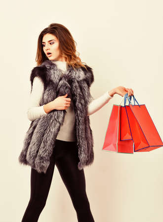 Girl makeup face wear fur vest white background. Lady hold shopping bags. Shopping concept. Fashionista buy clothes in shop. Sales and discount on black friday. Woman shopping luxury boutique Archivio Fotografico