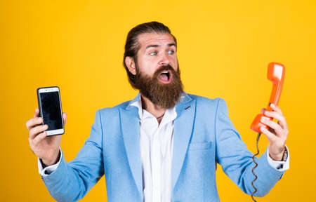 life meets possibilities. mature bearded man with retro phone. male hold smartphone. compare technology. mobile phone vs retro phone. business call. concept of technology progress. Then and Now