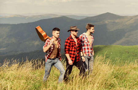 happy men friends with guitar. friendship. men with guitar in checkered shirt. group of people spend free time together