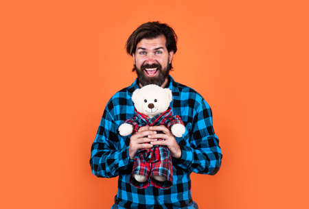 handsome hipster having playful mood. happy fathers day. mature man with bear toy. bearded man hold teddy bear. brutal guy with valentines day present Imagens
