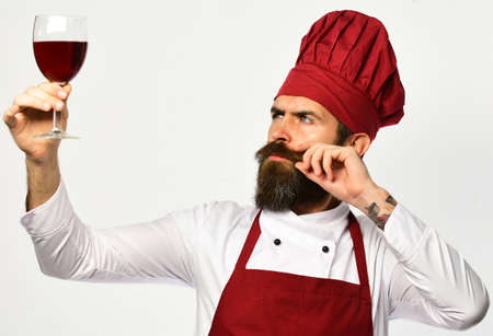 Chef holds glass of red wine up. Man with beard