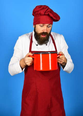 Kitchen utensils concept. Man with beard holds kitchenware