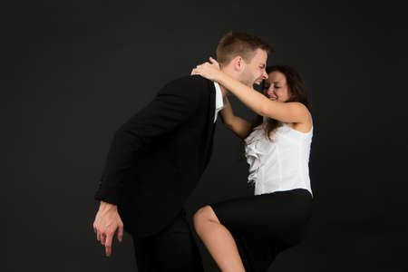 Violent woman in formal wear kneed businessman in groin dark background, violence