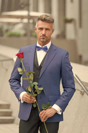 handsome boyfriend holding red rose. businessman hold red rose. elegant and confident man. groom in classic jacket. charismatic man wear wedding suit. Theatre and Opera. going in restaurant on date Banco de Imagens