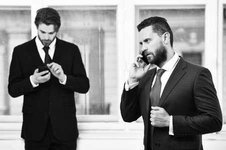 men or businessmen speaking on mobile phone near window