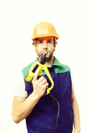 Builder with serious face expression, orange helmet and construction tool