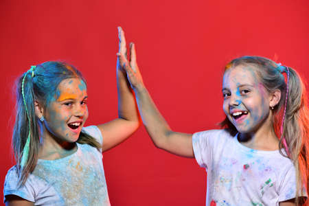Kids with ponytails make high fives. Schoolgirls have paint spots
