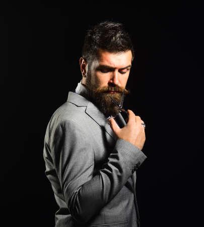 Man with beard holds steel scissors. Business and barbershop service 免版税图像