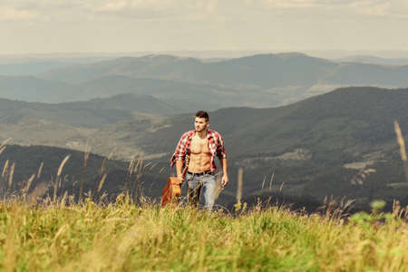 Power of Music. man with guitar in checkered shirt. hipster fashion. western camping and hiking. happy and free. cowboy man with muscular torso. acoustic guitar player. country music song Reklamní fotografie
