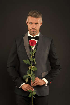 man dressed up in tuxedo with rose. Groom with tie and red rose. her elegant valentine. man tuxedo hold rose. man in tuxedo offers marriage. tailcoat or frac. red rose symbol of love. romantic love
