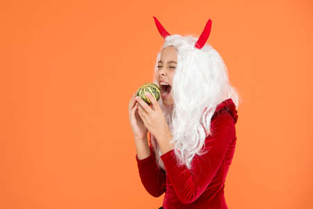 Just hanging out. happy halloween devil girl. childhood. hungry child in imp horns. kid has white hair bite pumpkin. jack o lantern. carnival costume party. trick or treat. celebrate the holidays