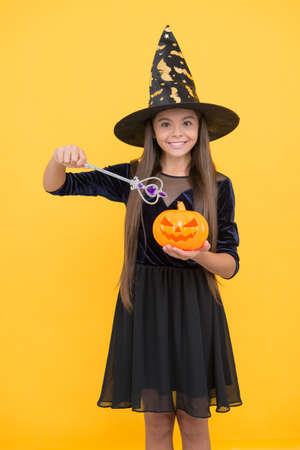 try a spell. kid create miracle with magic wand. carnival costume party. trick or treat. celebrate the holidays. jack o lantern. halloween witch girl. happy childhood. child in witch hat with pumpkin Stock Photo