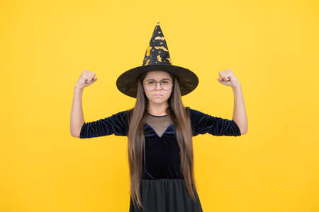 unhappy girl ready to celebrate. costume party fun. happy halloween. powerful child in witch hat and glasses. kid goes to wizard school. witchcraft and enchantment. childhood autumn holiday