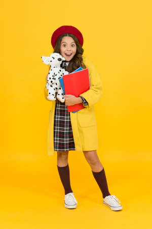 education concept. childhood happiness. school and fashion. child in pupil uniform. kid in french beret on yellow background. stylish teen college student. little girl with toy dog and notebooks