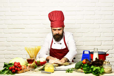 Cook with serious face in burgundy uniform sits by table