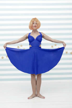 Fashion smiling woman shows blue dress skirt in dance shop. crazy woman in funny pose of ballerina dancer. funny crazy girl in dress stand in ballet position at dance shop. latest fashion