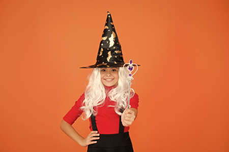 make wish. supernatural charmer. kid enchantress wave magic wand. happy halloween. believe in magic. smiling small girl halloween party. mystery witch do magic. small child witch hat. trick or treat